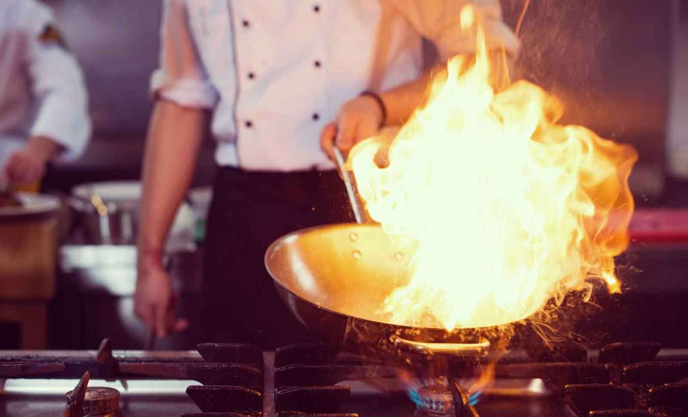 chef-doing-flambe-on-food-PF3STCY