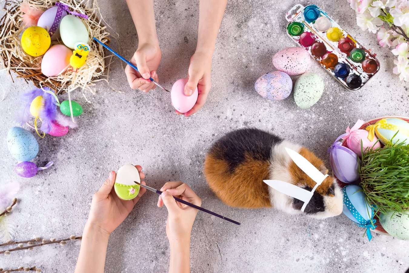 Preparing for Easter. Small children paint cookies and eggs with a guinea pig in the ears of a rabbit on the background of Easter attributes. Flat lay