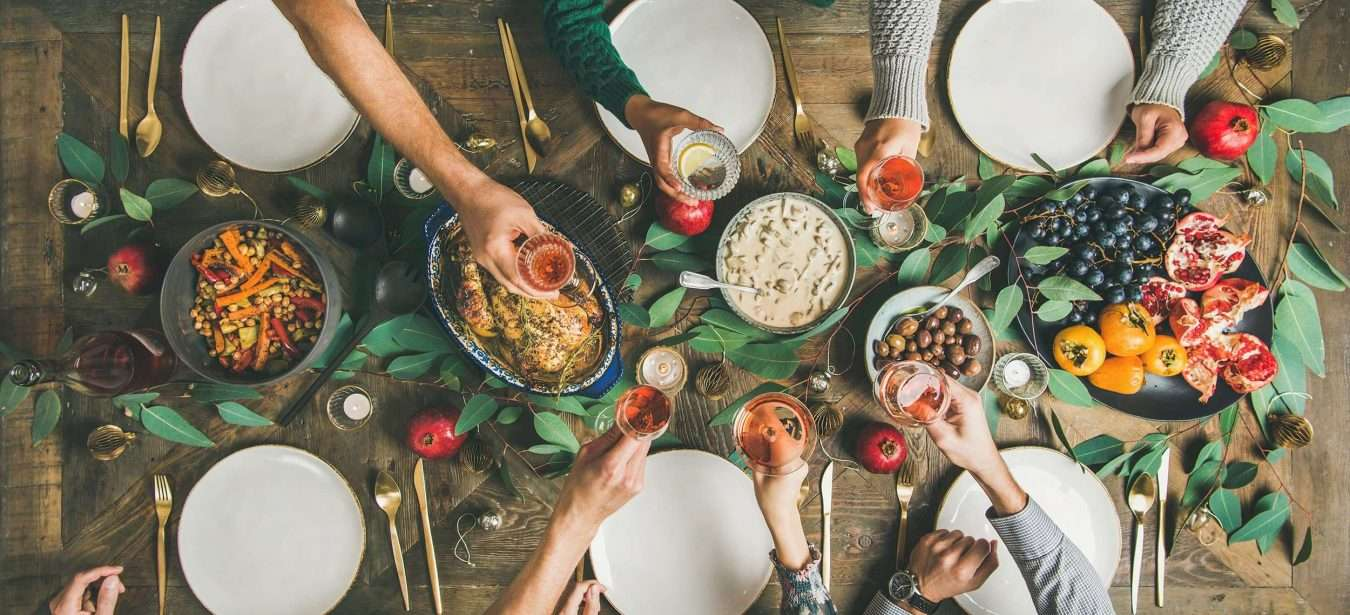 Traditional Christmas, New Year holiday celebration party. Flat-lay of friends or family feasting at festive table with turkey or chicken, vegetables, mushroom sauce, fruit, top view, wide composition